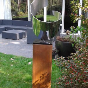 abstract stainless steel artwork placed in garden