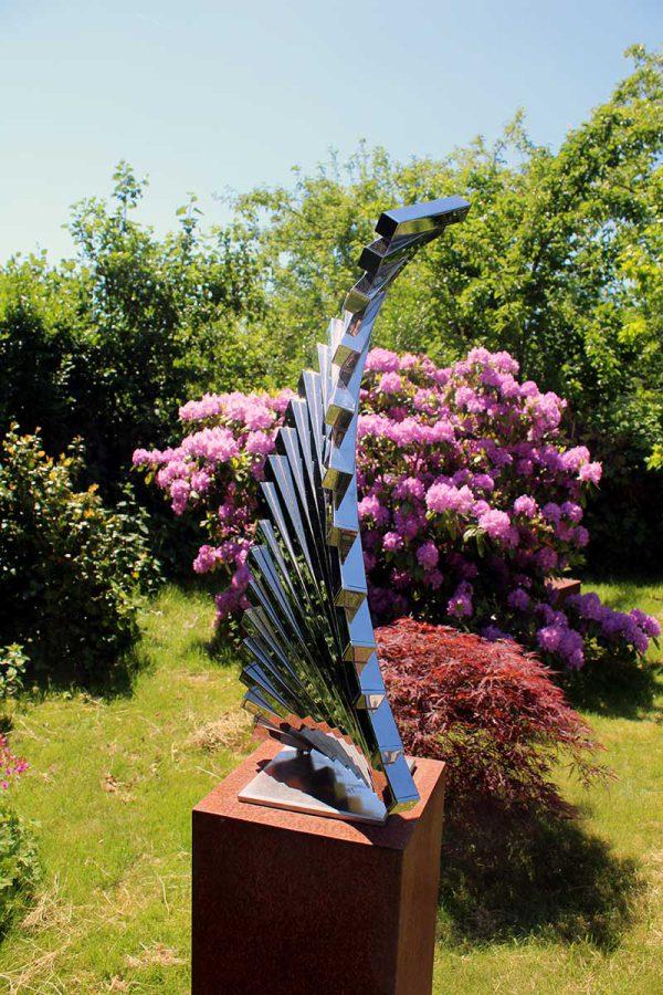 modern RVS kunstwerk in zomerse tuin